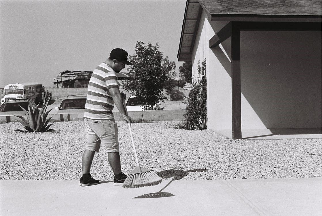 A man sweeping outside the side