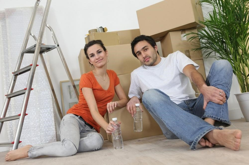 a couple sitting inside an apartment